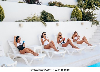 fashion outdoor photo of beautiful sexy women  in elegant swimming suits posing near swimming suit in luxurious white villa