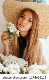 fashion outdoor photo of beautiful sexy woman with blond hair in elegant dress and straw hat posing with white tender flowers