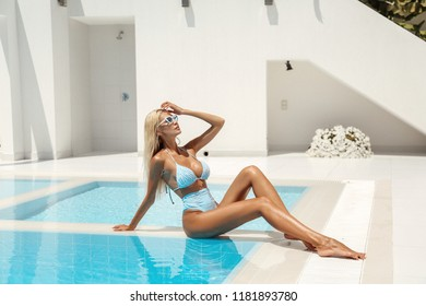 fashion outdoor photo of beautiful sexy woman with blond hair in elegant swimming suit posing near swimming pool in luxurious white villa