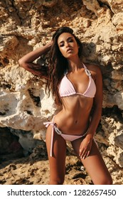 fashion outdoor photo of beautiful sexy girl with dark hair in elegant swimming suit posing on the summer beach among the rocks