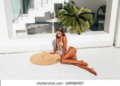 fashion outdoor photo of beautiful sexy woman with long blond hair in elegant swimming suit and accessories relaxing at luxurious white villa