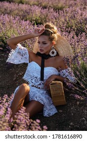 fashion outdoor photo of beautiful sexy woman with blond hair in elegant clothes with accessories posing in blooming lavender fields