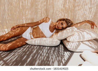 fashion outdoor photo of beautiful sexy woman with blond hair in elegant swimming suit relaxing under the sun in wicker chair