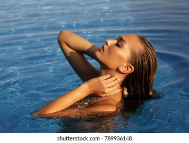 fashion outdoor photo of beautiful sexy girl with blond hair in luxurious swimming suit relaxing in swimming pool