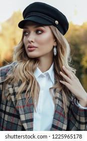 fashion outdoor photo of beautiful woman with blond hair in elegant outfit and hat posing in autumn park