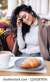 fashion outdoor photo of beautiful woman with dark hair in elegant clothes posing in the street cafe