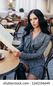 fashion outdoor photo of beautiful woman with blond hair in elegant clothes posing in cafe, drinking a coffee with dessert