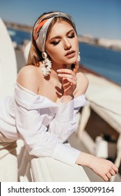 fashion outdoor photo of beautiful woman with blond hair in elegant outfit with silk headband posing near the sea