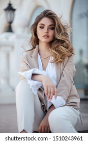 fashion outdoor photo of beautiful woman with blond hair in elegant clothes and accessories posing in summer park