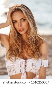 fashion outdoor photo of beautiful woman with blond hair in beach clothes relaxing on the summer beach