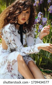 fashion outdoor photo of beautiful woman with dark curly hair in elegant dress and straw hat posing in summer garden