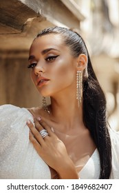 fashion outdoor photo of beautiful woman with dark hair in luxurious wedding dress and accessories posing in the summer street