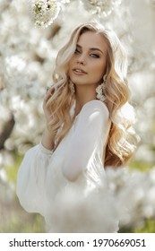fashion outdoor photo of beautiful woman with blond hair in elegant dress posing in blooming garden