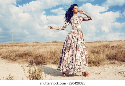 fashion outdoor photo of beautiful woman with dark curly hair in luxurious floral dress posing in summer field