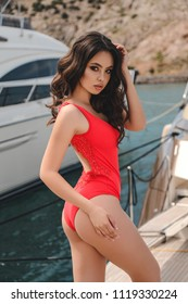 fashion outdoor photo of beautiful young woman with dark hair in elegant swimming suit posing near yachts in pier