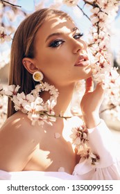 fashion outdoor photo of beautiful young woman with blond hair in elegant dress and luxurious earrings posing in garden with flowering peach trees