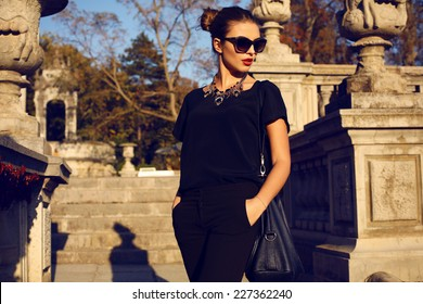 fashion outdoor photo of beautiful young woman with dark hair in elegant clothes and sunglasses posing in sunny autumn park
