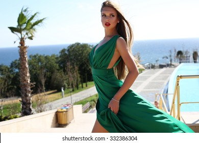 fashion outdoor photo of beautiful young woman with long blond hair in luxurious green silk dress posing beside swimming pool