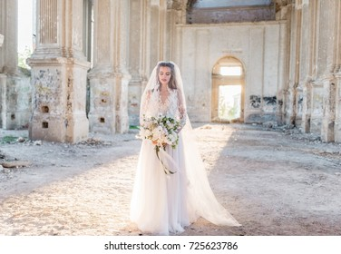 Fashion outdoor photo of beautiful young bride in elegant wedding dress. Marriage portrait of gorgeous long hair woman in white bridal dress posing outdoors