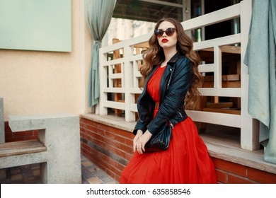 Fashion outdoor photo of gorgeous long hair woman in elegant red dress and black leather jacket. Fashionable hipster girl in trendy clothes posing at city street lifestyle portrait.
