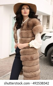 fashion outdoor photo of gorgeous sensual woman with dark hair in elegant clothes and luxurious fur coat, walking by autumn city