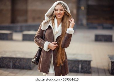 fashion outdoor photo of gorgeous sensual woman with blond hair in elegant clothes and luxurious coat, walking by winter city