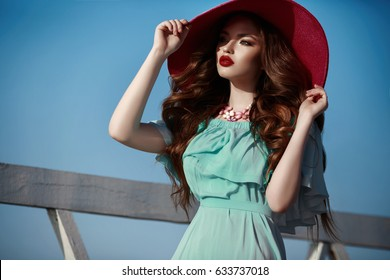 Fashion outdoor photo of gorgeous sensual woman in summer hat with ginger hair in elegant blue dress over sky, walking the city. Vogue style model posing outdoors at beach summer look.