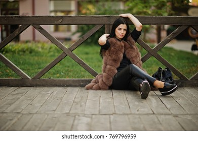 Fashion outdoor photo of gorgeous sensual woman with dark hair in elegant clothes and luxurious fur coat sitting against wooden railings.
