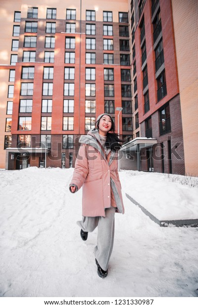 fashion outdoor photo of gorgeous sensual korean woman with black hair in clothes  walking by winter city