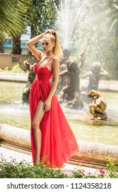 Fashion outdoor photo of gorgeous sexy woman with blond hair in red maxi dress posing in spring garden with water fountain.