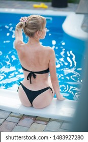 fashion outdoor photo of gorgeous sexy girl with blond hair in swimsuit relaxing near swimming pool