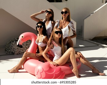 fashion outdoor photo of gorgeous sexy girls in swimsuits relaxing near swimming pool