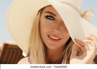 fashion outdoor photo of gorgeous sexy woman with blond hair in elegant swimsuit and white hat posing at summer beach