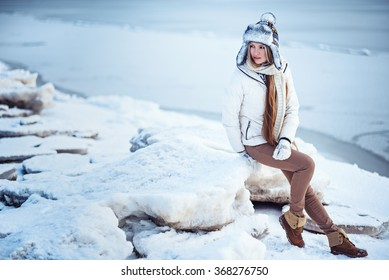 fashion outdoor photo of gorgeous woman with long blonde hair wears luxurious white coat, posing on an ice floe