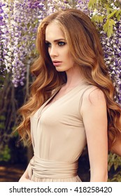 fashion outdoor photo of gorgeous woman with luxurious hair in elegant dress, posing in blossom spring garden