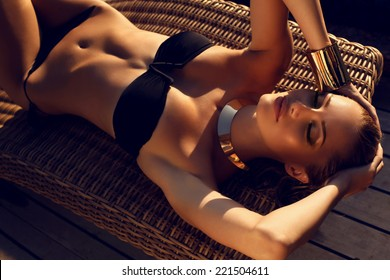 fashion outdoor photo of sexy beautiful woman with blond hair in elegant black bikini with accessories relaxing on summer beach