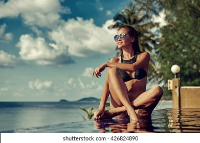 Fashion outdoor photo of sexy beautiful woman with long hair in elegant black bikini with accessories relaxing on summer beach
