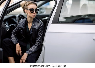 fashion outdoor photo of sexy beautiful woman with dark hair in black leather jacket and sunglasses posing in luxurious auto