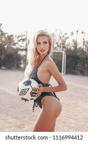fashion outdoor photo of sexy football cheerleader girl with long blond hair in elegant swimming suit, posing with soccer ball on the beach