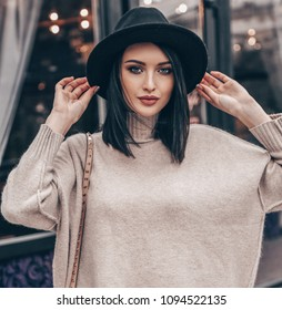 fashion outdoor photo of young pretty woman with short dark hair in elegant outfit and black hat walking on the street