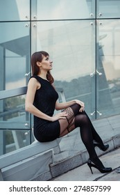 Fashion outdoor portrait of sexy beautiful woman with brown hair wearing in black dress, hose and high heels. Posing on creative urban background.