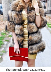 Fashion outdoor style portrait of young beautiful elegant woman in golden dress and brown luxurious fur coat holding red handbag walking on city street