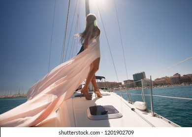 Fashion outdoor summer photo of sexy woman in luxurious dress relaxing on a sailing yacht floating on the sea against sunshine and beach.