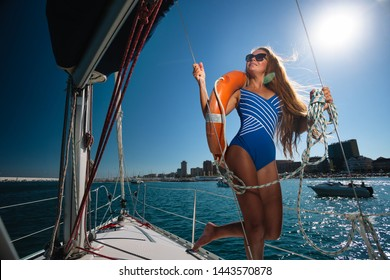 Fashion outdoor summer photo of sexy woman in luxurious bikini relaxing on a sailing yacht floating on the sea against the background of cliffs and beach.