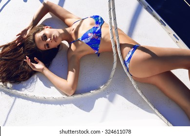 Fashion outdoor summer photo of sexy beautiful woman with dark hair and slim sexy body wearing a swimsuit, relaxing and sunbathing on a yacht at a luxury resort