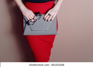 Fashion outfit details. Young stylish woman in red sexy skirt with black and white striped clutch bag