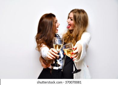 Fashion party portrait of elegant funny sister girls having fun laughing and gossip, ready for celebration drinking champagne, black and white glamour party,bright makeup , joy, emotions, cheers.
