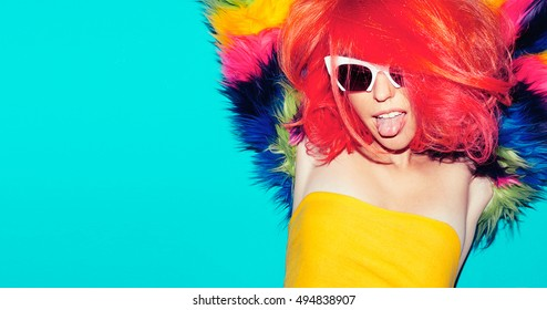 Fashion party time. Playful Girl with bright red hair and fur coat.