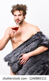 Fashion and pathos. Rich athlete enjoy his life. Richness and luxury concept. Sexy sleepy rich macho tousled hair drink wine isolated on white. Guy attractive rich posing fur coat on naked body.