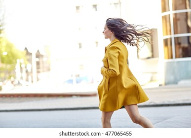 fashion and people concept - happy young woman in coat running along on city street